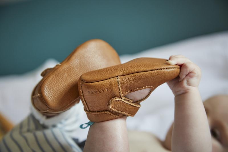 bébé portant des chaussons en cuir souple César marron attrapant ses pieds