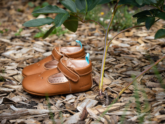 Chaussons bébé en cuir souple César marron posés sur des copeaux de bois