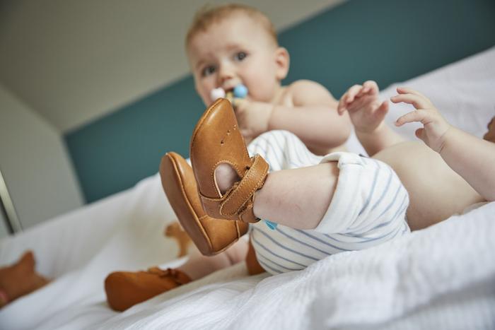 jambes de bébé portant des chaussons souples en cuir César marron