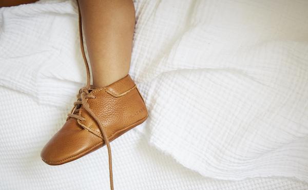 pied de bébé portant des chaussons en cuir souple Colombe marron avec lacets marrons défaits