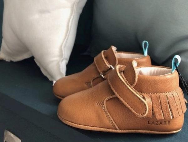 chaussons bébé en cuir souple marron à franges sur canapé