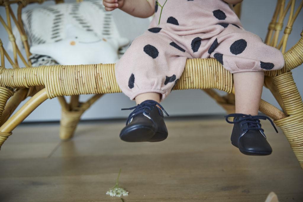 enfant assis sur fauteuil portant les chaussons en cuir souple bleu marine du modèle colombe