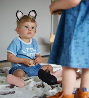 petite fille assise par terre avec chaussons en cuir rose et pyjama bleu