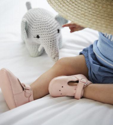 petite fille avec chapeau assise sur un lit avec chausson bébé en cuir rose