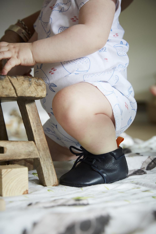 petit garçon à genoux avec chaussons en cuir soupe bleu marine