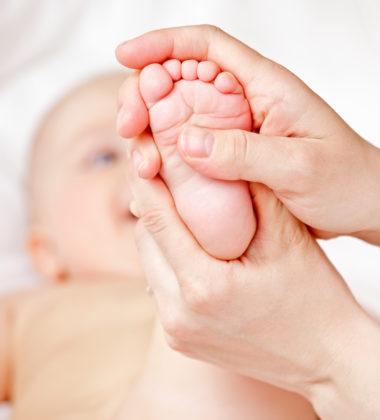 bébé qui se fait masser les pieds