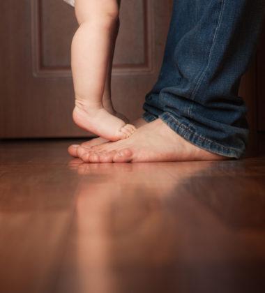 bebe qui marche sur les pieds d'un adulte