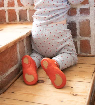 bébé en pyjama assis sur ses genoux dans les escaliers portant des chaussons en cuir souple rouge avec une semelle partie antidérapante en caoutchouc