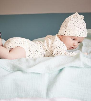 bébé allongé sur le ventre portant des chaussons en cuir souple César bleu marine