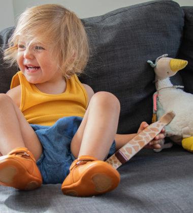 petite fille bebe assise sur un canapé avec des chaussons en cuir souple semelles antidérapantes