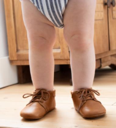jambes de bébé debout avec des chaussons à lacets en cuir souple marron