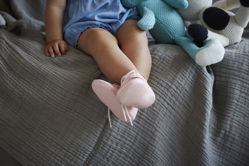 fille assise sur genoux avec chaussons en cuir rose