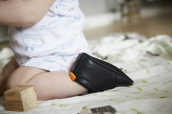 bébé assis sur ses genoux et portant des chaussons bébé en cuir souple bleu marine