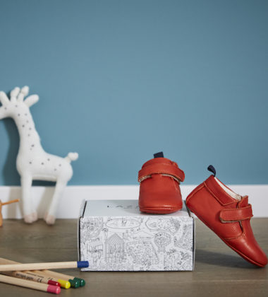 Chaussons bébé Achille rouge en cuir souple sur une boite à chaussures