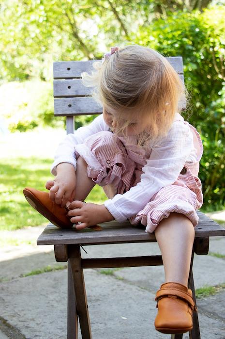 petite fille assise sur une chaise dehors en train d'enfiler des chaussons en cuir souple Achille marron à scratch