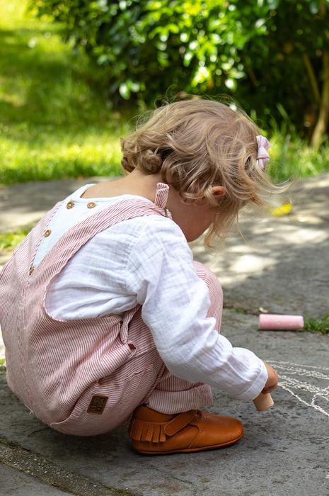 petite fille accroupie avec des chaussons en cuir souple marron à franges sur talon