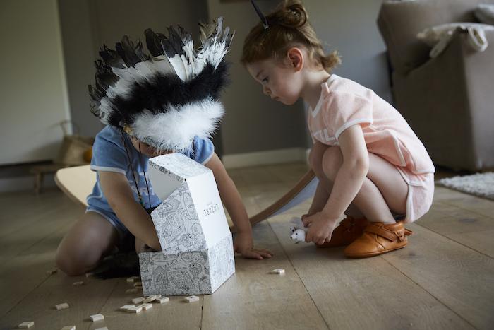 deux enfants accroupis jouant avec des lettres en bois