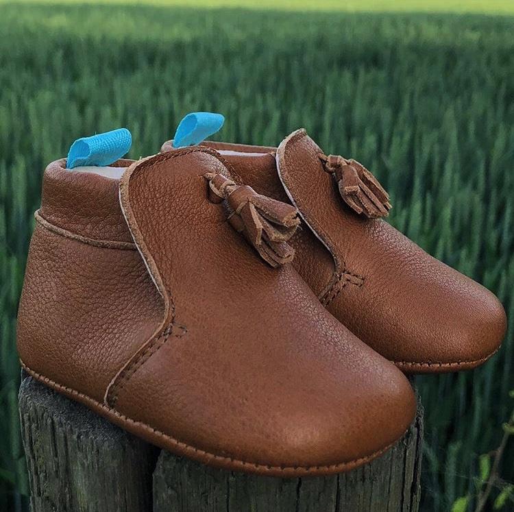 chausson en cuir souple marron posés sur un morceau de bois