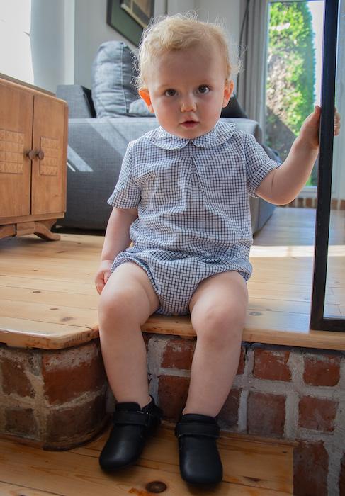 bébé assis sur une marche portant des chaussons en cuir souple bleu marine