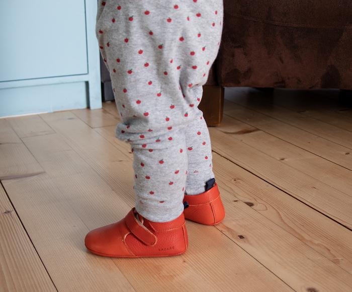 jambes de bébé en pyjama portant des chaussons en cuir souple Achille rouge