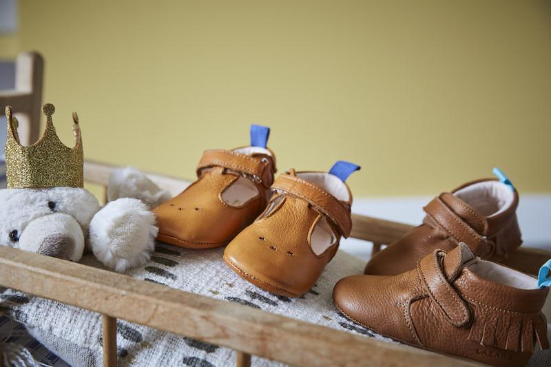 chaussons en cuir souple César Camel et Eliot marron à franges posés sur un lit