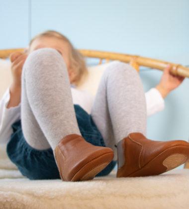 Petite fille assise dans un fauteuil portant des chaussons en cuir souple marron élastique gris