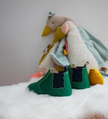 paire de chaussons en forme de boots verte sur peau lainée et peluches en arrière plan