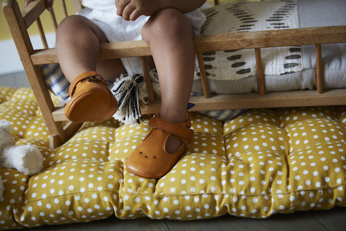 jambes de bébé portant des chaussons en cuir souple César camel