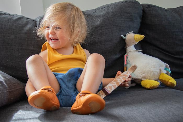 enfant sur le canapé avec peluche portant des chaussons en cuir souple camel