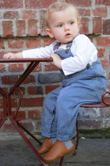 petit garçon assis à une table de jardin portant une salopette et des chaussons en cuir souple Oscar marron élastique gris
