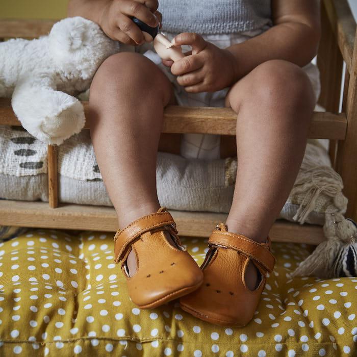 jambes de bébé sortant d'un berceau portant des chaussons en cuir souple César camel