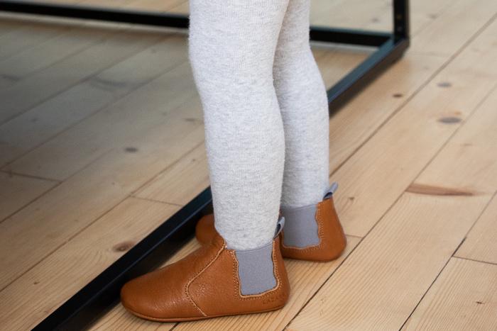 jambe d'enfant portant des chaussons en cuir souple Oscar marron élastique gris