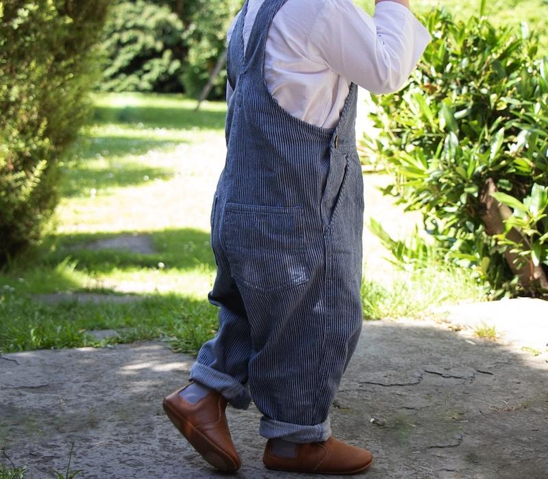 enfant debout en salopette dehors portant des chaussons en cuir Oscar marron élastique gris