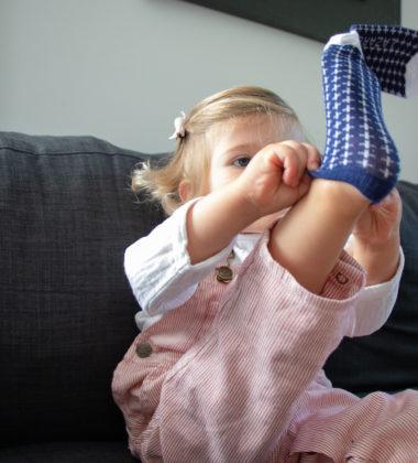 petite fille en train d'enfiler des chaussettes bleu