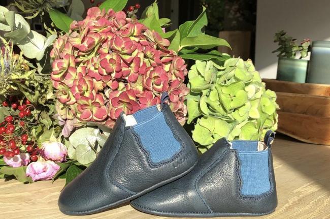chausson en cuir souple bleu marine avec fleurs en arrière plan