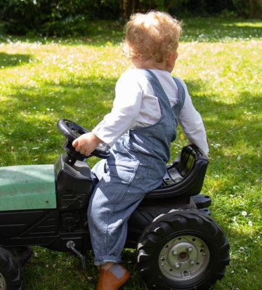 enfant assis sur un jouet tracteur