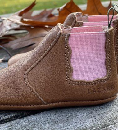 chaussons bébé en cuir souple Oscar marron, élastique rose sur les cotés et languette kaki posés sur des planches de bois