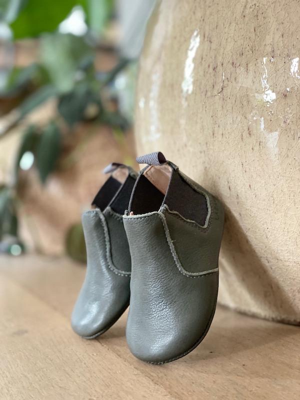 chausson en cuir gris posé sur un mur
