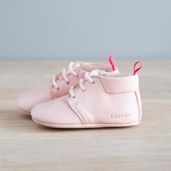 chausson bébé rose de coté sur bois