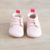 Chausson bébé rose sur table en bois