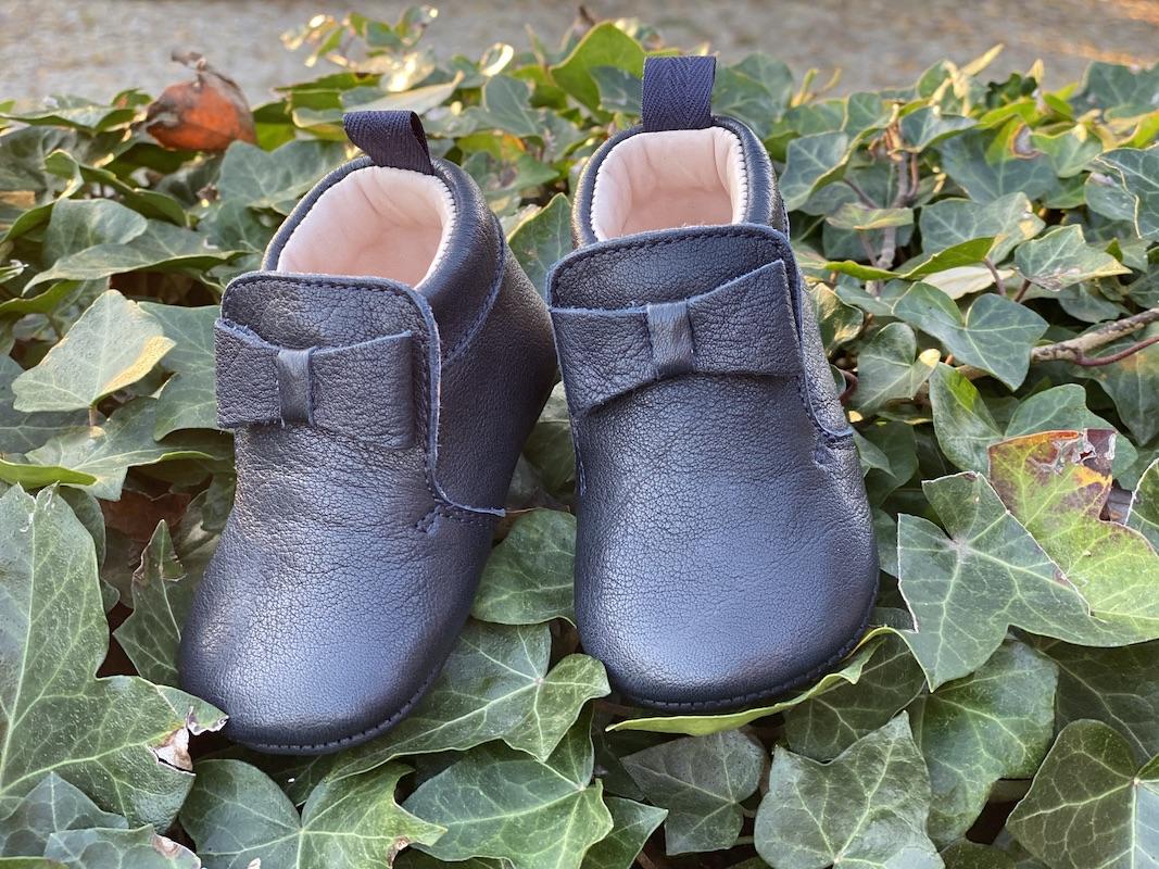chaussons bébé en cuir souple Arielle bleu marine posés sur des feuilles