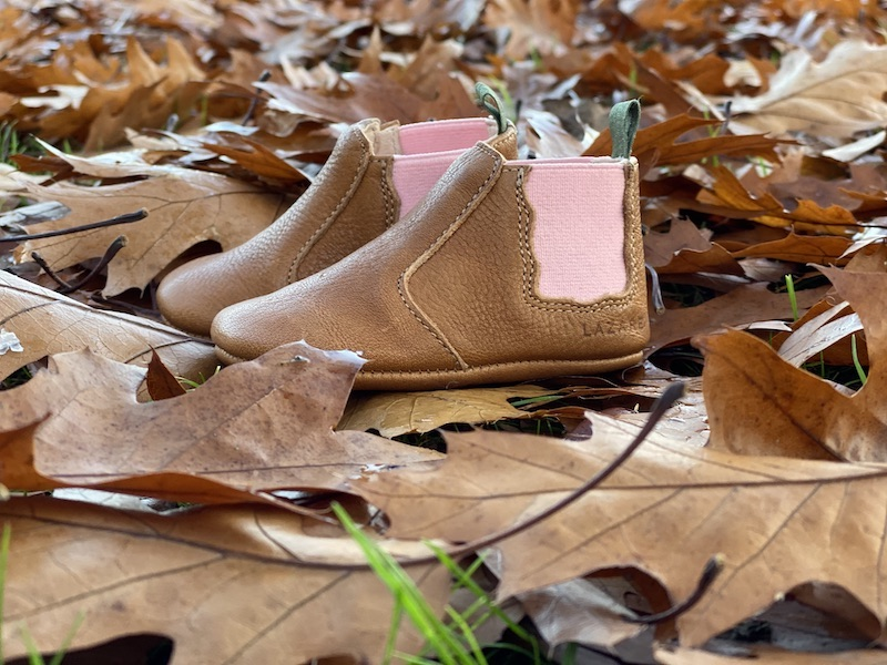 chaussons bébé en cuir souple Oscar marron, élastique rose sur les cotés et languette kaki posés sur des feuilles d'automne