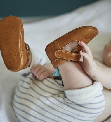 bebe attrape ses pieds sur un lit