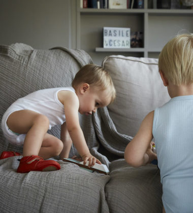 petit garçon accroupi dans un canapé portant des chaussons en cuir souple Achille rouge