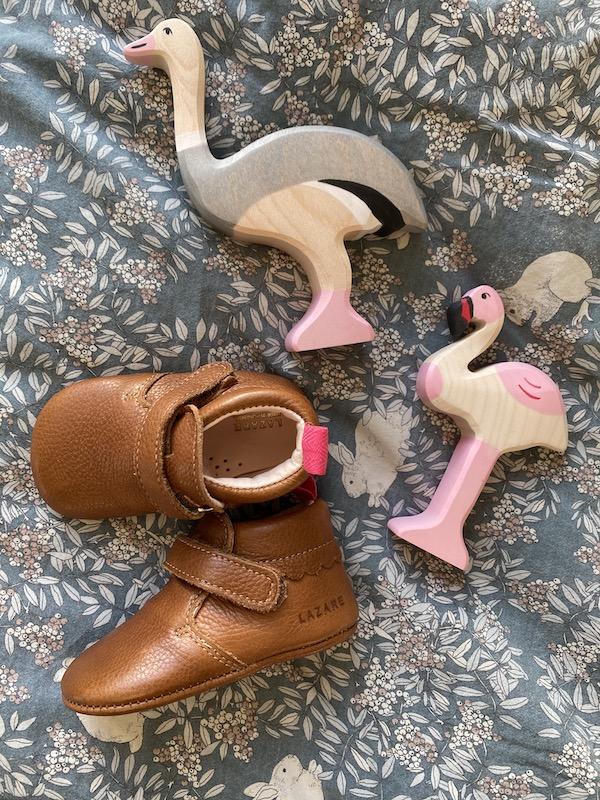 chaussons bébé Suzanne marron en cuir souple posés sur un drap avec des oiseaux en bois en décoration