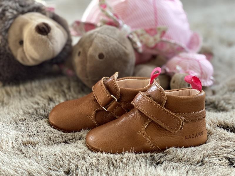 chaussons bébé en cuir souple Suzanne marron posés sur un plaid avec des peluches en fond