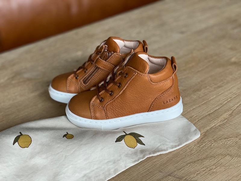 chaussures premiers pas Auguste marron en cuir souple et lacets posées sur une table