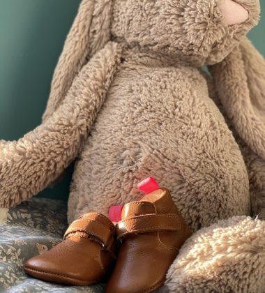 chaussons bébé Suzanne en cuir souple marron posés devant un lapin en peluche