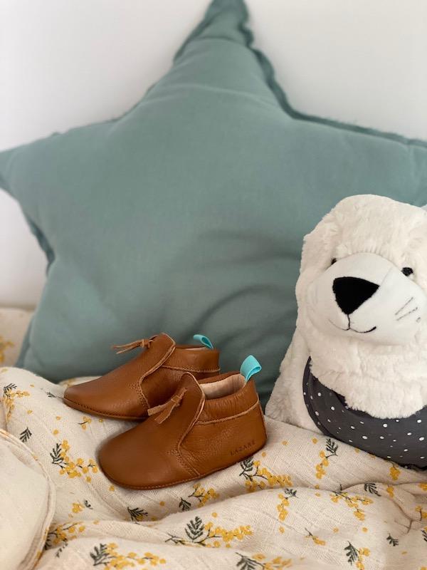 chaussons bébé en cuir souple marron Madeleine avec pompon sur le dessus posé sur un foulard avec coussin étoile en fond