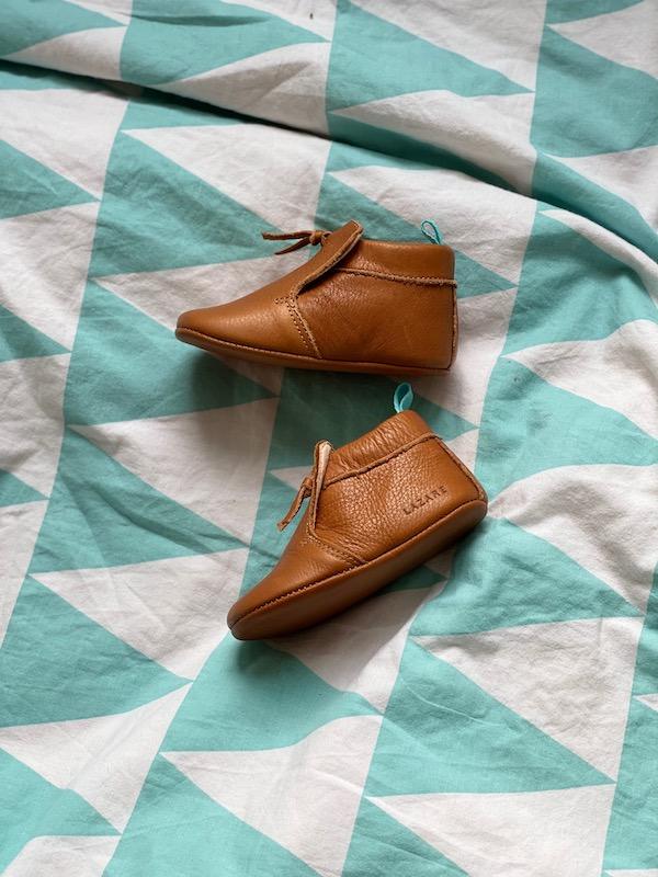 chaussons bébé en cuir souple marron Madeleine avec pompon sur le dessus posés sur un lit